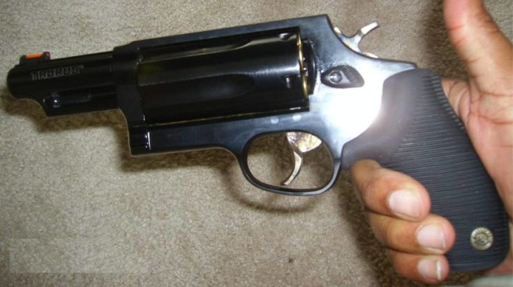 Focused shot on hand holding a Taurus Judge ble steel body.