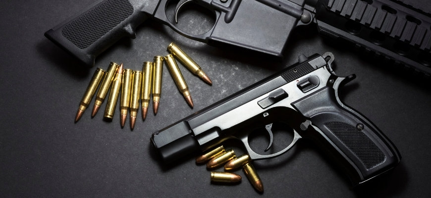 Guns and bullets in black background