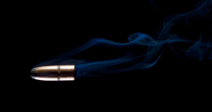 Copper bullet with blue smoke behind on a black background