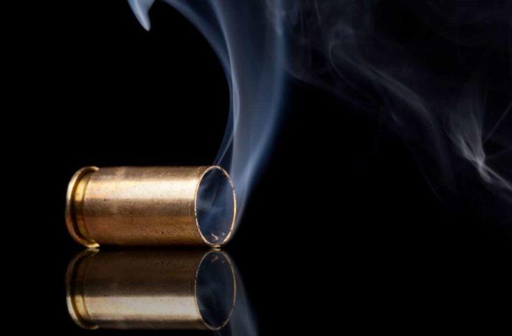 Smoking 9mm bullet casing over black background