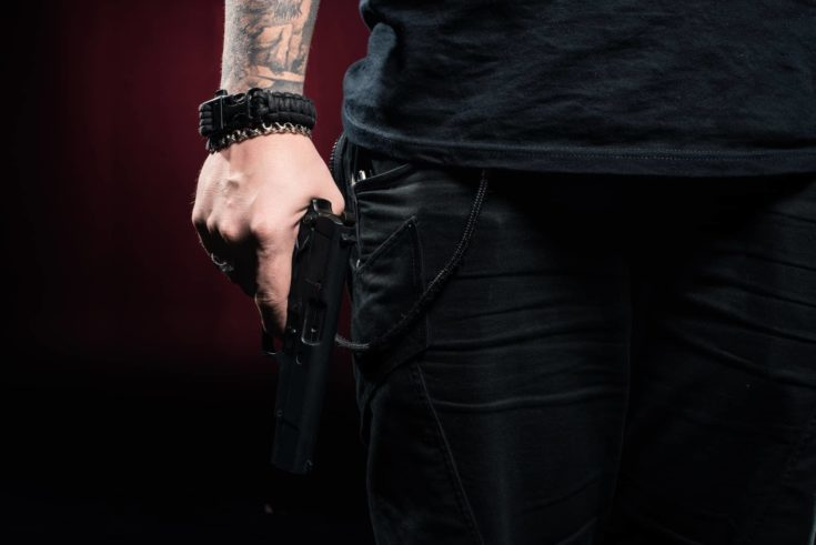 Close-up view of gun in male hand on red background