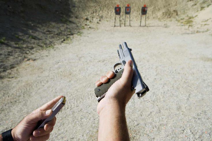Close up of man's hand reloading handgun at training