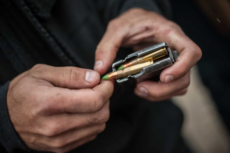 Close-up top macro view of soldier hands load rifle machine gun bullets into cartridge clip