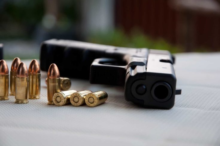 Bullets and a gun laying on a whitesheet.