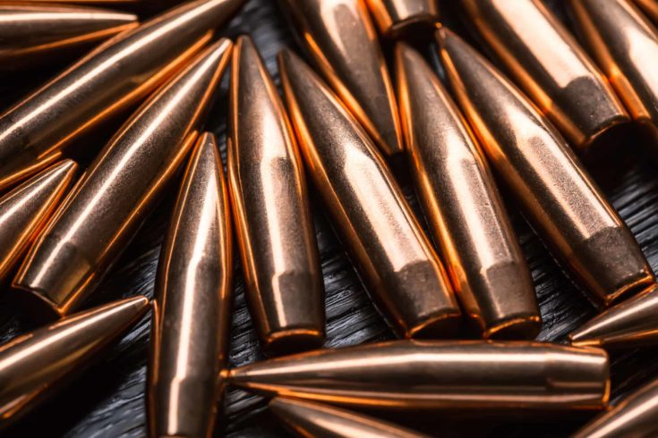 Placer copper bullets on a dark wooden background, shot in the studio.