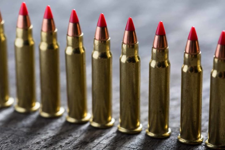 Cartridges ranked with red tip on a dark wooden background