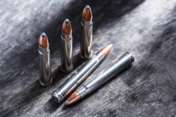 Cartridges silver with copper large-caliber bullets in a gray textural composition on wooden background.