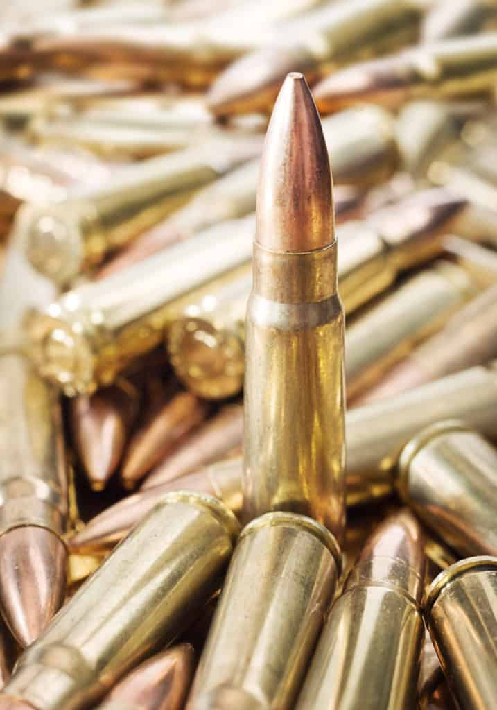 Standing rifle cartridge in pile of ammo