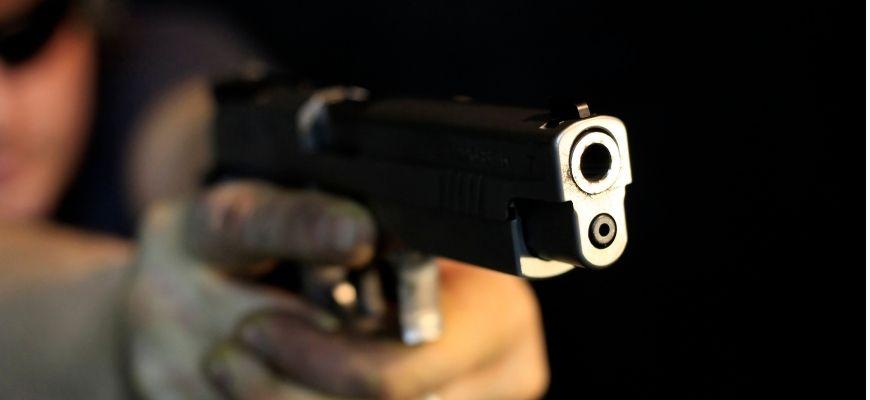 Man holding a gun in black background