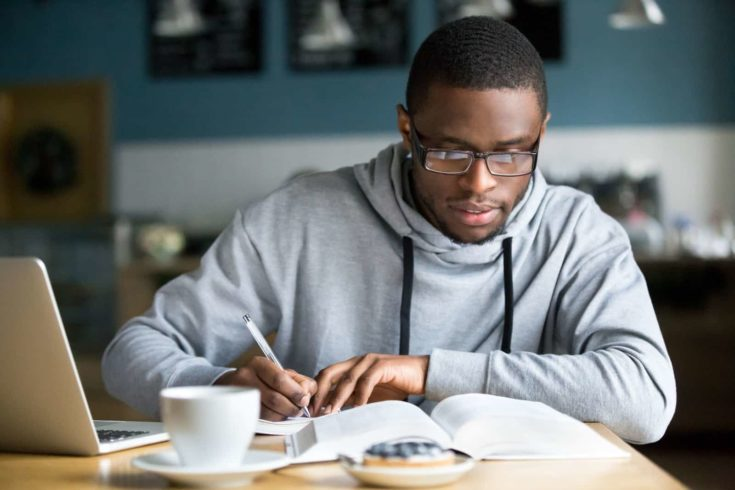 Focused millennial african american student in glasses making notes writing down information from book