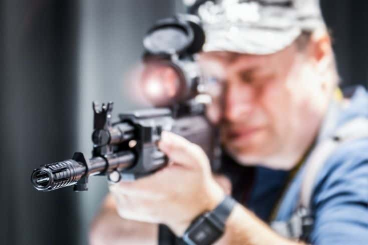 Guy aiming a rifle with a Compensators
